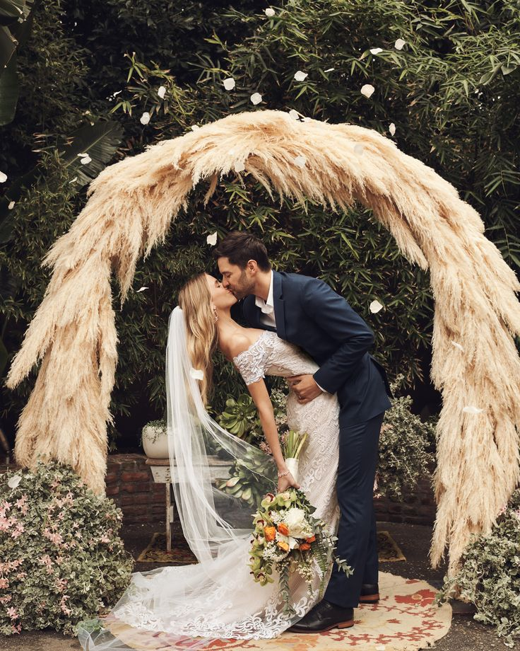 a romantic kiss wedding photo before pampas grass arch