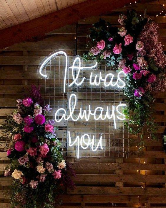 small and intimate floral wedding ideas with neon signs for some modernity