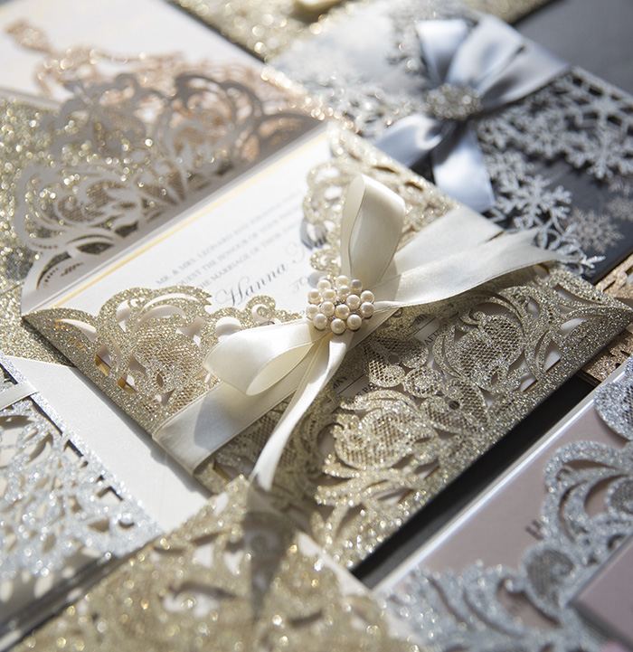 champagne gold laser cut wedding invites with ribbon and pearls