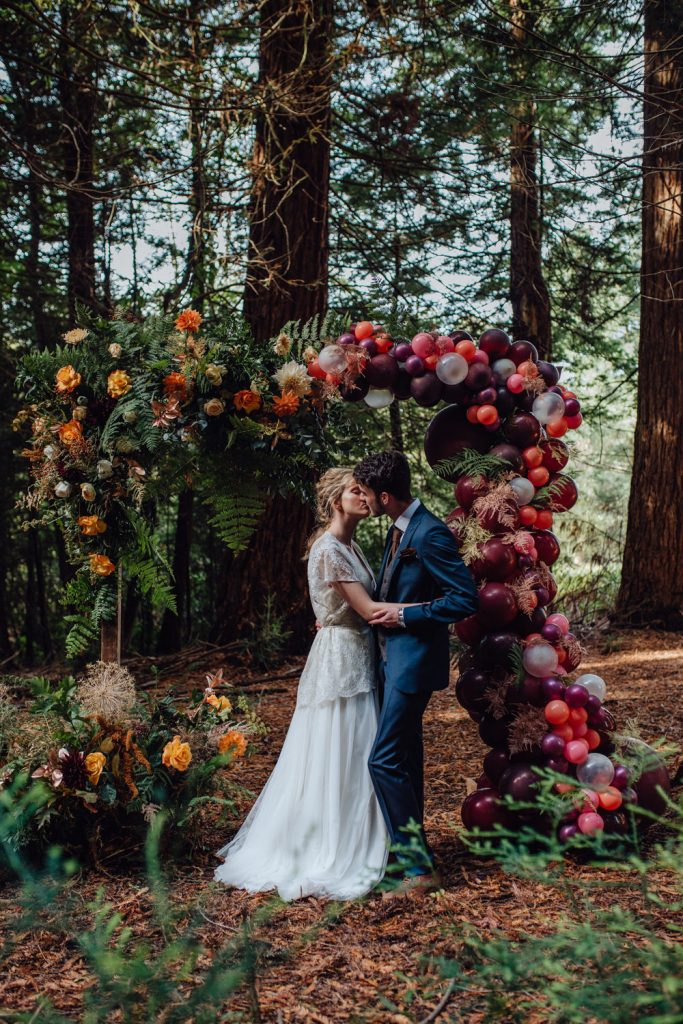 creative bold color flowers and ballons fall rustic wedding arches