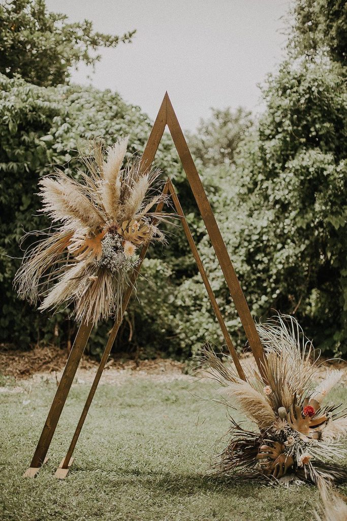 modern outdoor triangle metal wedding altar with pampas grass decoration