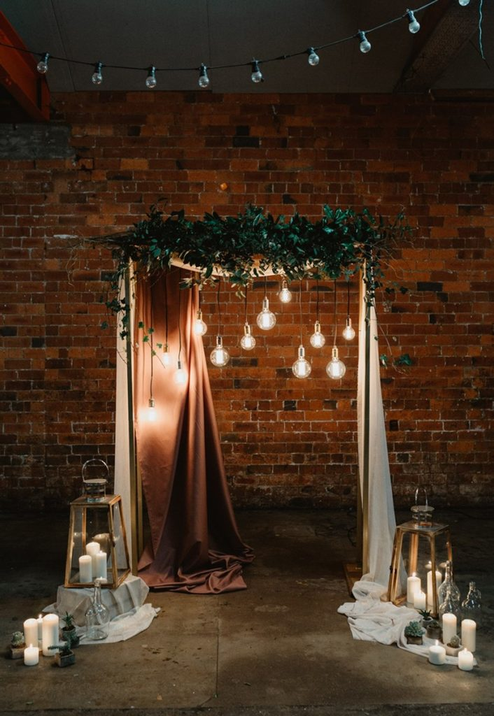 unusual industrial wedding ceremony arbor with edison bulb lights