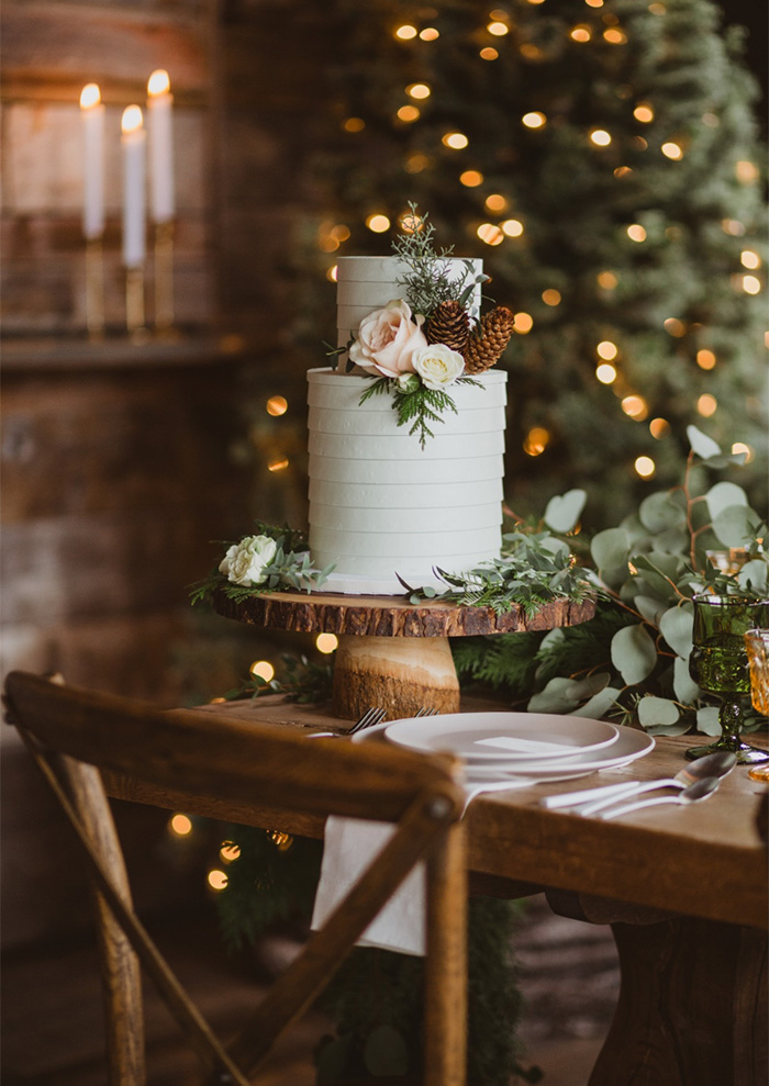 white small two-tier wdding cake with pines and flowers
