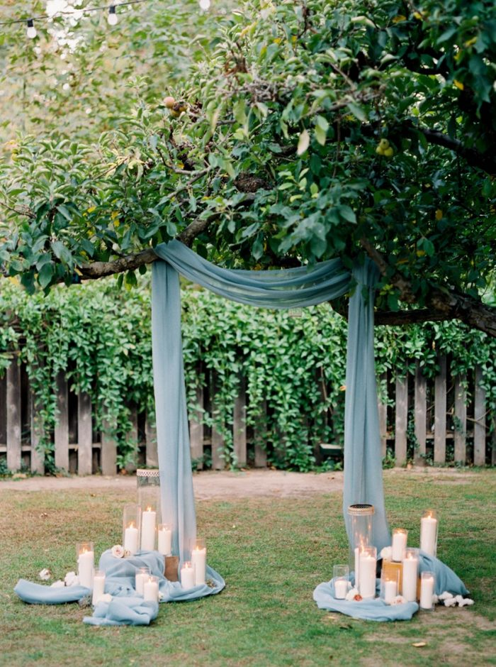 beautiful blue draped wedding ceremony backdrop with candle lights