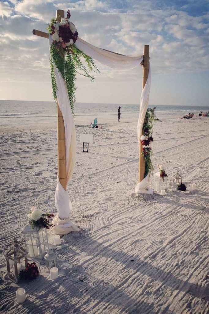 burgundy and white floral wedding arch with fabric in beach wedding