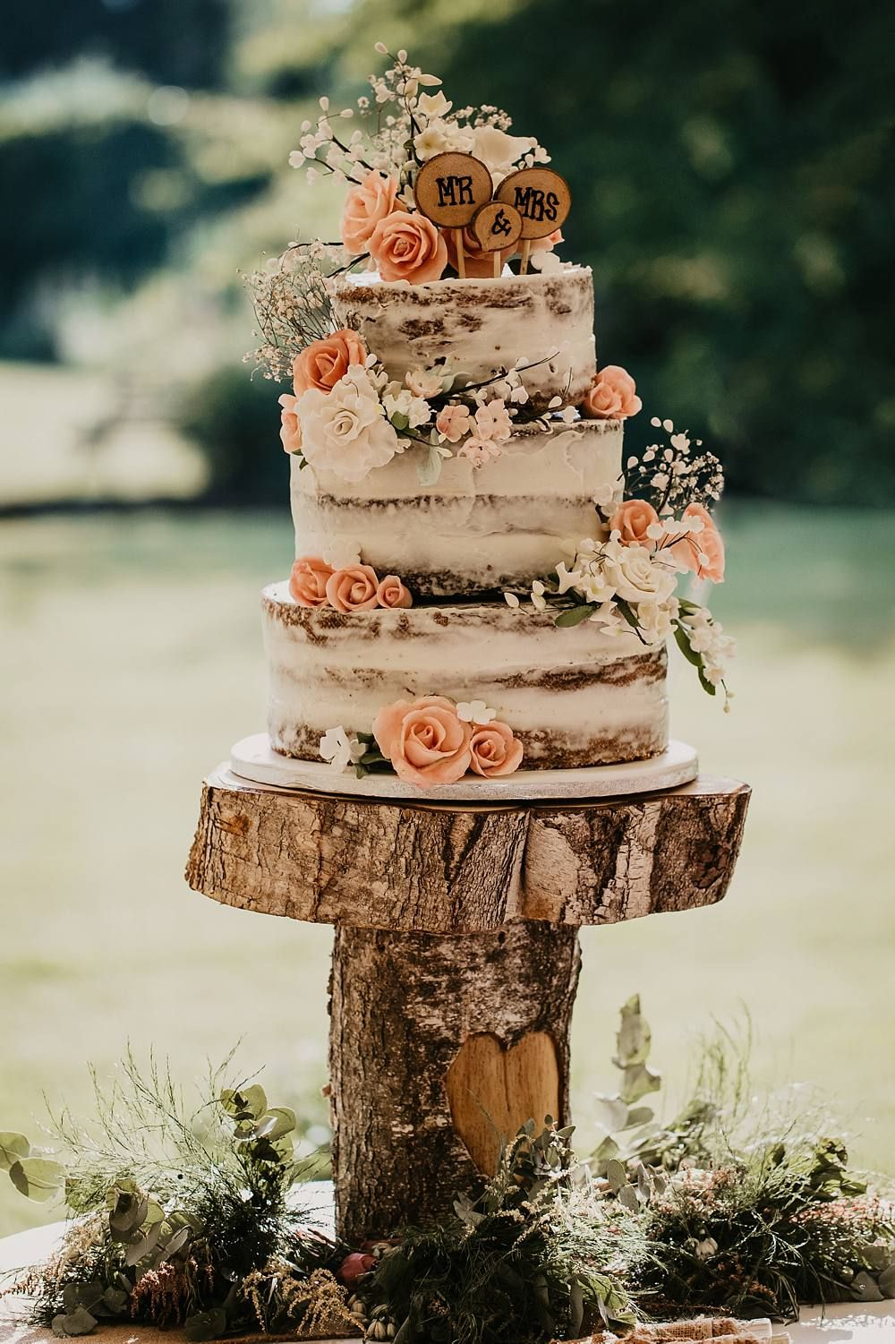 rustic pink flower wedding cake with wood stump stand