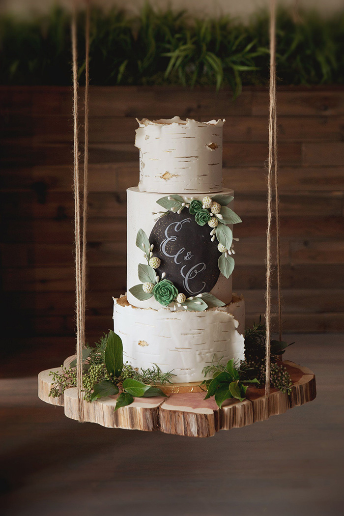 special suspended white and greenery wedding cake on wood slice