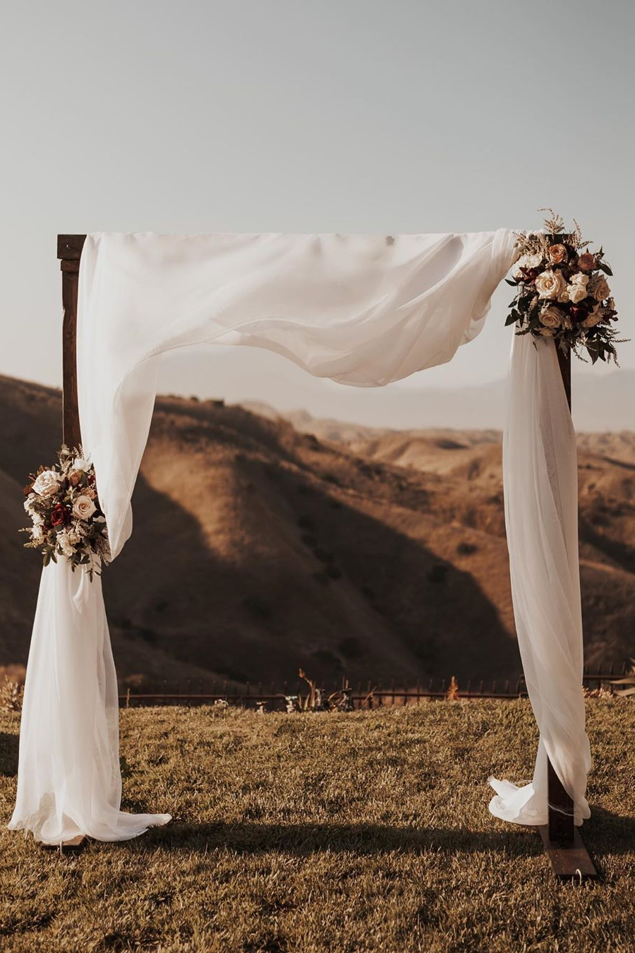 unique dried flower wedding arch with white flowy voile