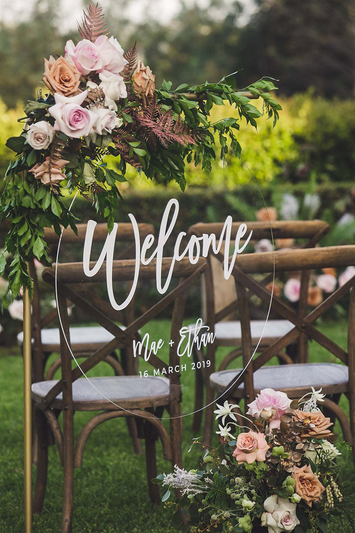 circular clear acrylic wedding welcome sign with flowers