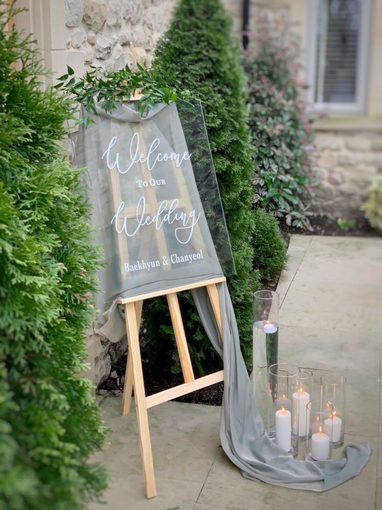 elegant lucite and acrylic wedding welcome sign with grey drapery