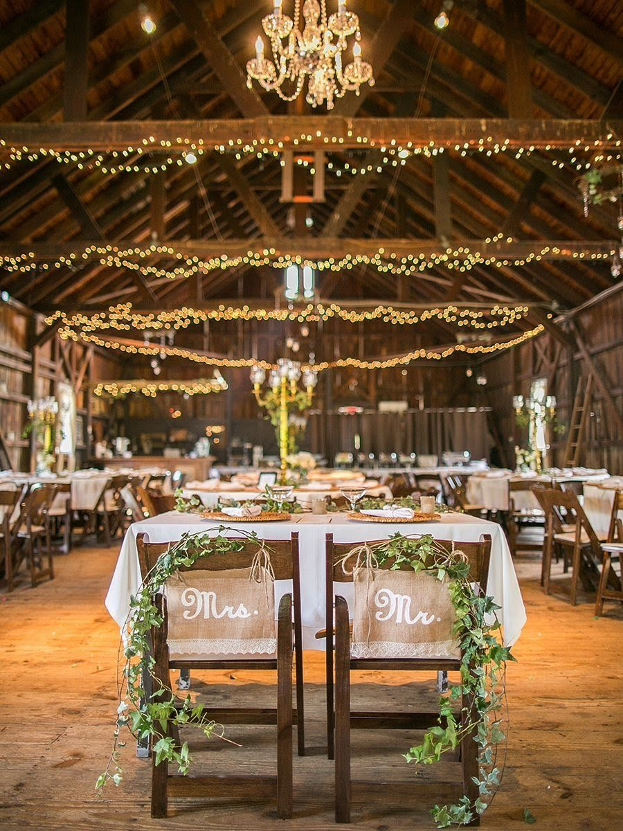 rustic barn wedding groom and bride chair signs wtih green garlands