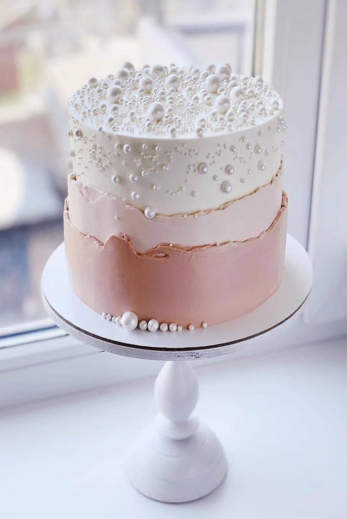 small blush and white wedding cake with pearls