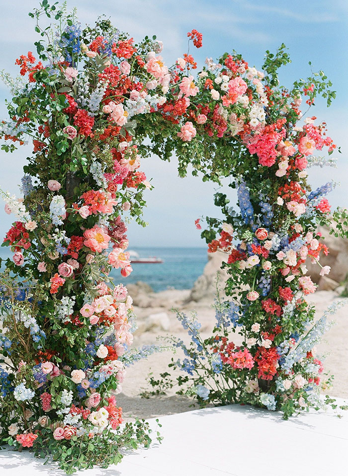 magical oceanside summer wedding arch with fresh red and blue