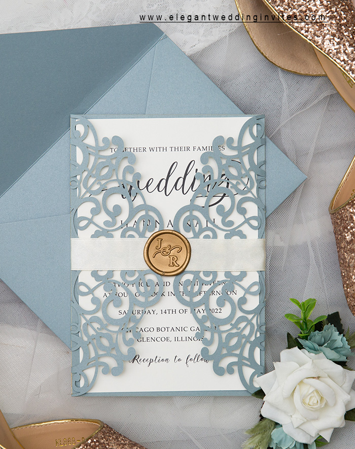 elegant dusty blue laser cut wedding invitation with gold wax seal and ribbon tie