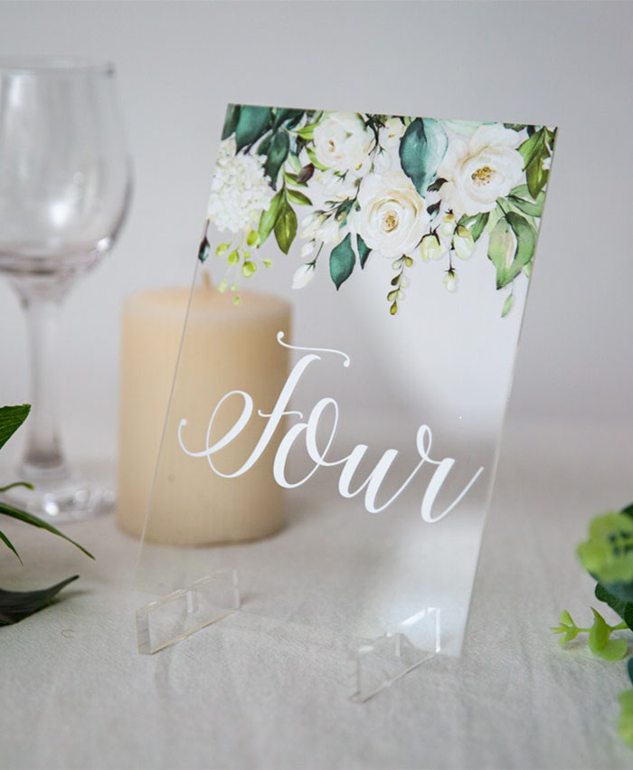 greenery and white floral acrylic wedding signs
