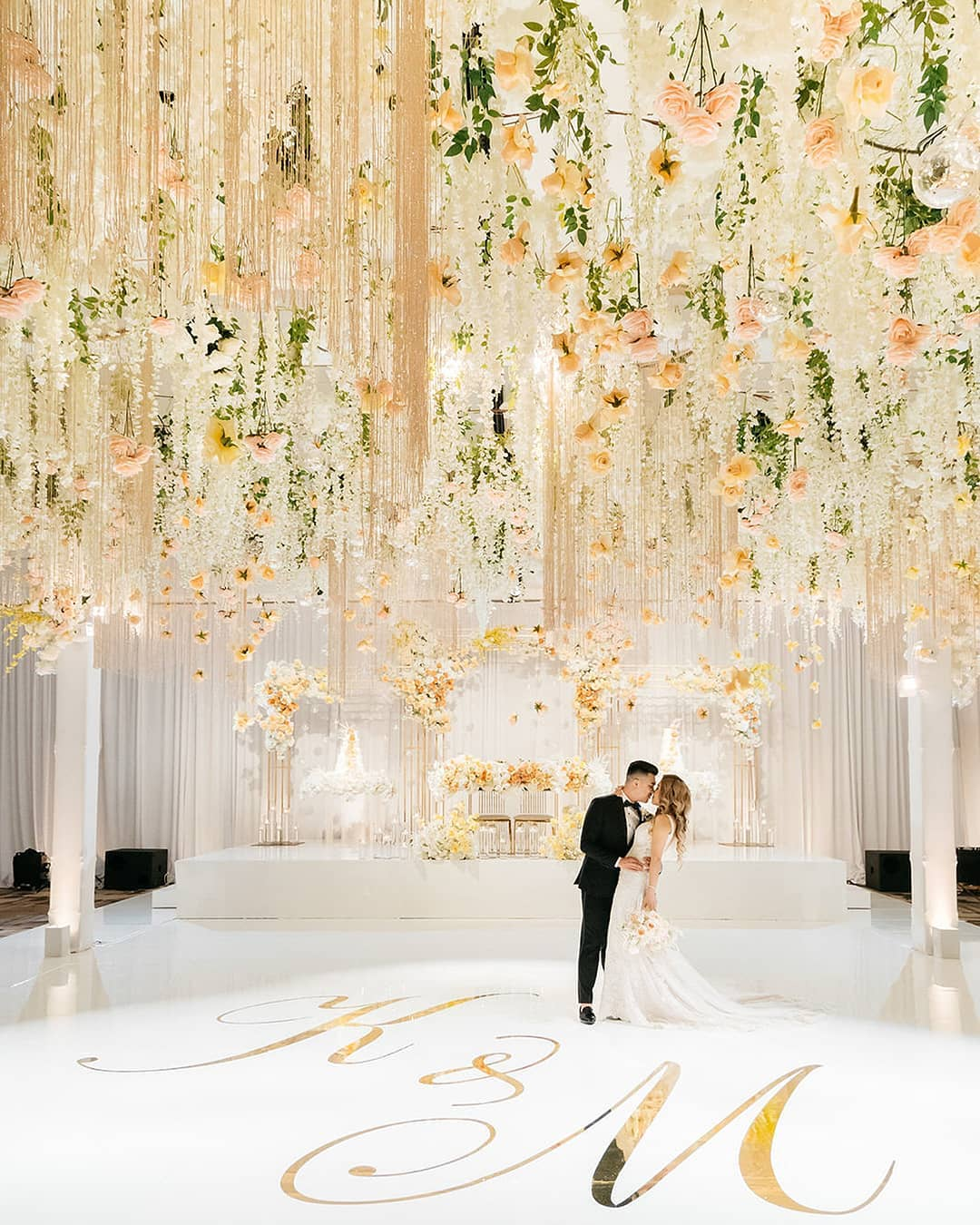 glamorous white banquet hall wedding with hanging flowers and up lightings