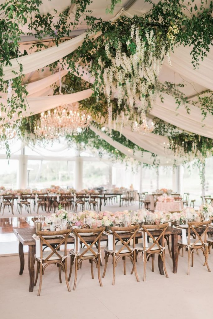 rustic glam theme tented wedding with blush draping and green garlands